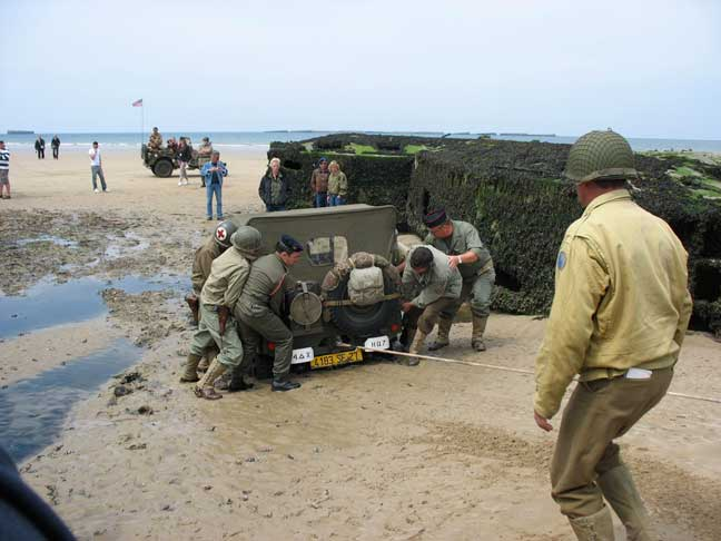 Is this a great picture or what? You would think we staged it. We didn't. This guy thought he could drive between the caissons. Little did he know that this is where the sewer water is let out into the channel from Arromanches. They tried a jeep first, no go. Then they tried a GMC with this tow rope and the guys help. SNAP! A new nylon tow strap and the GMC freed him, but what came out with him chased us all back. The stench that came out with this jeep was nasty. More pictures of this debacle and what ensued on the album link.